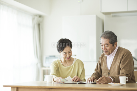 パンフレットを見ながら会話をするシニア夫婦の写真素材 [FYI01622383]