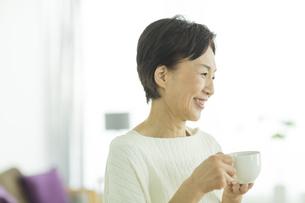 コーヒーカップを持った笑顔のシニア女性の写真素材 [FYI01622386]