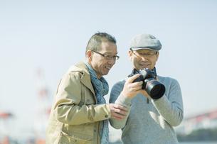一眼レフカメラで写真を見るシニア男性の写真素材 [FYI01622406]