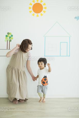 壁のイラストの前に立つ親子の写真素材 [FYI01622412]