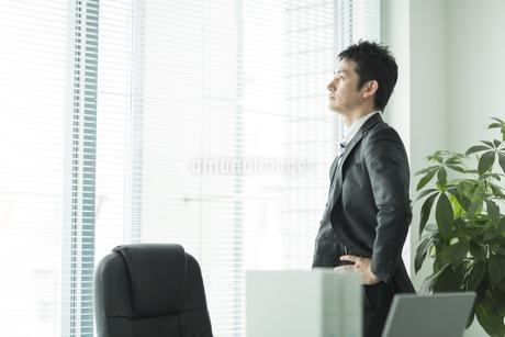 窓辺に立ち外を見るビジネスマンの写真素材 [FYI01622418]