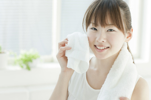 汗を拭く若い女性の写真素材 [FYI01622423]