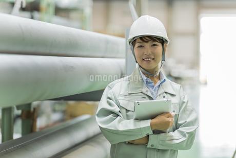 工場で働く作業服の女性の写真素材 [FYI01622425]