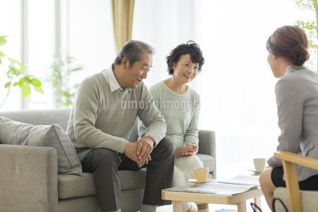 商談をするシニア夫婦とビジネスウーマンの写真素材 [FYI01622434]