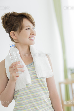 ペットボトルの水を持って笑顔の女性の写真素材 [FYI01622454]