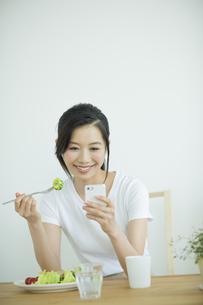 朝食を食べながらスマートフォンを見る女性の写真素材 [FYI01622456]