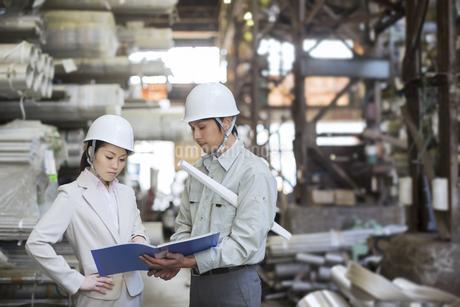 倉庫で打ち合わせをする男女の社員の写真素材 [FYI01622459]