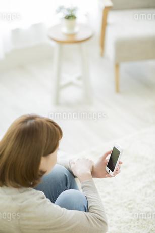 スマートフォンを見る若い女性の写真素材 [FYI01622460]