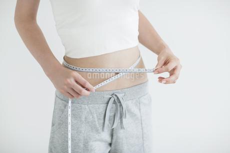 メジャーでウエストを測る女性の写真素材 [FYI01622463]