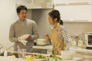 キッチンで調理をする夫婦の写真素材 [FYI01622472]