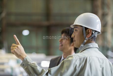 商品を指差して話す男性社員の写真素材 [FYI01622477]