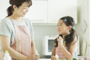 母親に切った野菜を見せる女の子の写真素材 [FYI01622479]