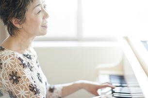 ピアノを弾き歌を歌う中高年女性の写真素材 [FYI01622489]