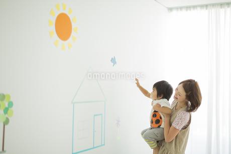 壁のイラストの前で遊ぶ親子の写真素材 [FYI01622490]