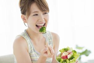 サラダを食べる笑顔の女性の写真素材 [FYI01622493]