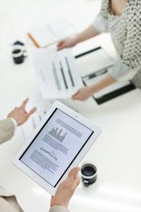 タブレットPCで打ち合わせをするビジネスマンとビジネスウーマンの写真素材 [FYI01622503]