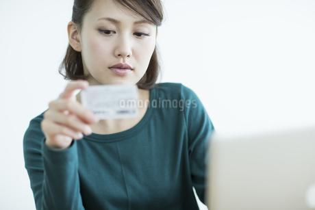 パソコンをしながらカードを見る女性の写真素材 [FYI01622509]