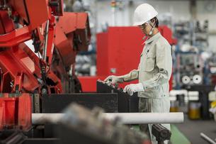 機械を操作する作業服の男性の写真素材 [FYI01622516]