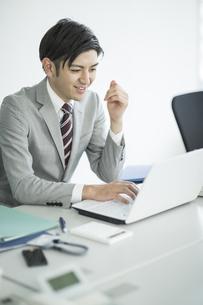 笑顔でパソコンを見るビジネスマンの写真素材 [FYI01622523]