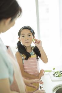母親に切った野菜を見せる女の子の写真素材 [FYI01622525]