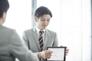 タブレットPCを使用して打ち合わせをするビジネスマンの写真素材 [FYI01622526]