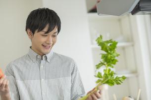 キッチンで野菜を持つ笑顔の若い男性の写真素材 [FYI01622527]