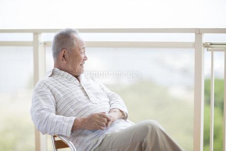 バルコニーで笑顔のシニア男性の写真素材 [FYI01622533]