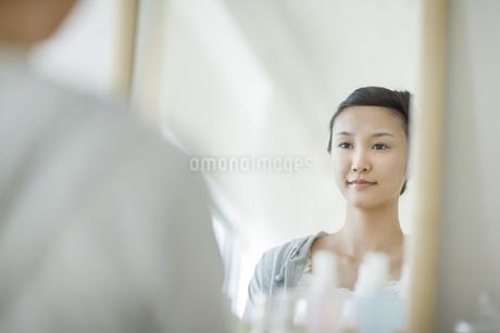 鏡を見る若い女性のスキンケアイメージの写真素材 [FYI01622535]