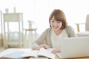 部屋で勉強をする若い女性の写真素材 [FYI01622537]