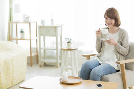 部屋でティータイムの若い女性の写真素材 [FYI01622545]