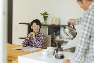 コーヒーを入れる夫を見るシニア女性の写真素材 [FYI01622596]