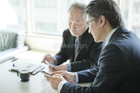スマートフォンを操作するビジネスマンの写真素材 [FYI01622605]