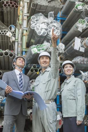 倉庫で商品を指差して見る男女の社員の写真素材 [FYI01622607]