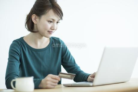 パソコンをしながらクレジットカードを持つ女性の写真素材 [FYI01622630]