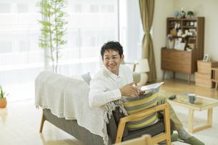 タブレットPCを持って笑顔の男性の写真素材 [FYI01622632]