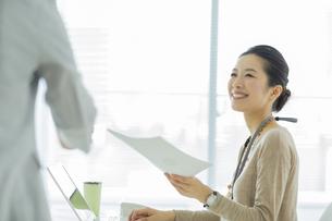 笑顔で書類を受け取るビジネスウーマンの写真素材 [FYI01622637]