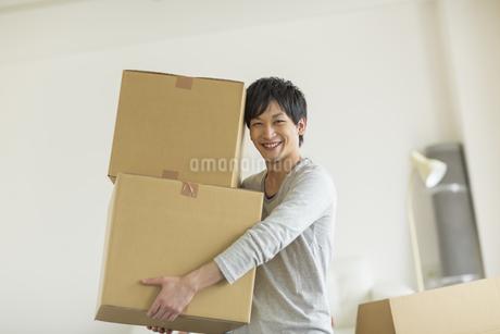引っ越しのダンボールを運ぶ若い男性の写真素材 [FYI01622658]