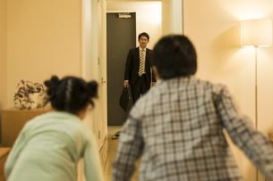 帰宅した父親に駆け寄る子供たちの写真素材 [FYI01622663]