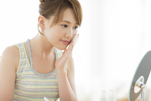 コットンを頬にあてて鏡を見る女性の写真素材 [FYI01622665]