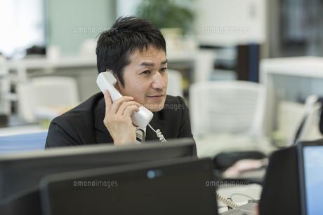 デスクで電話をするビジネスマンの写真素材 [FYI01622671]