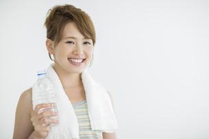 ペットボトルの水を持って笑顔の女性の写真素材 [FYI01622678]
