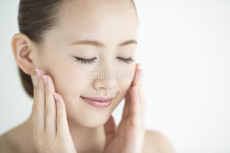 頬に手をあてる女性のスキンケアイメージの写真素材 [FYI01622684]