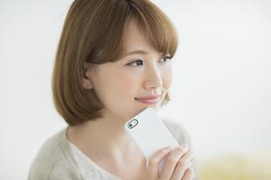 携帯電話を顎にあてて考える女性の写真素材 [FYI01622697]