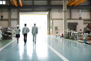 工場で歩く男女作業員の後姿の写真素材 [FYI01622701]