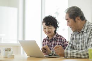 ノートパソコンを見ながら会話をするシニア夫婦の写真素材 [FYI01622709]