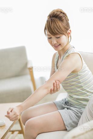 腕にクリームを塗る女性の写真素材 [FYI01622716]