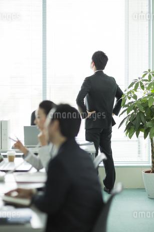 窓辺に立ち外を見るビジネスマンの写真素材 [FYI01622719]