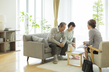 商談をするシニア夫婦とビジネスウーマンの写真素材 [FYI01622726]