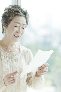 窓際で手紙を読む中高年女性の写真素材 [FYI01622747]