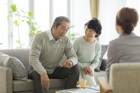 商談をするシニア夫婦とビジネスウーマンの写真素材 [FYI01622749]